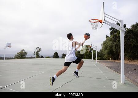 Les adolescents de sexe masculin de basket-ball jumping avec balle vers de basket-ball Banque D'Images