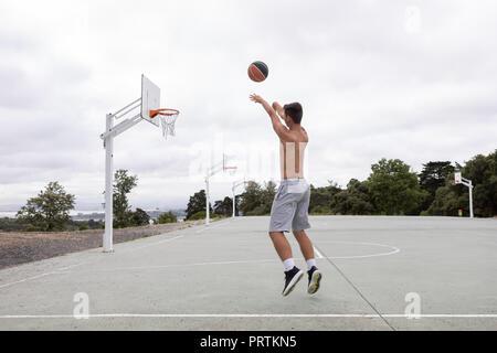 Les adolescents de sexe masculin de basket-ball du saut et du lancer de balle de basket-ball Banque D'Images