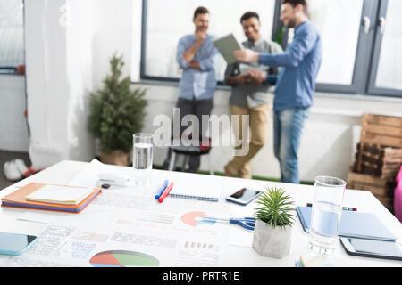 Close-up view of business charts et des fournitures de bureau sur 24 et les hommes d'affaires, debout derrière le concept d'équipe Banque D'Images