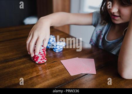 Cartes de jeu de fille à table, l'empilement des jetons, Close up Banque D'Images