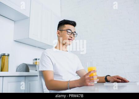 Low angle view of smiling young asian man holding glass lunettes en jus fo et regardant en bas alors qu'il était assis dans la cuisine Banque D'Images