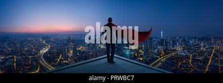 Homme d'affaires en costume et cape hero stand à toit à la grande ville voir et penser plan d'affaires de l'avenir . Scène de nuit . Banque D'Images