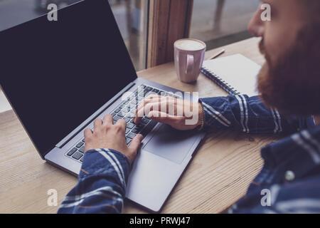 Portrait de jeune homme clavardage par net-book pendant le travail d'art. Banque D'Images