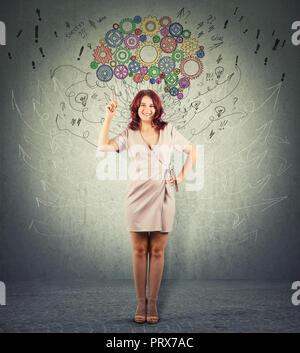 Portrait d'une jeune femme rousse fabricants pointée vers le haut, une main sur les hanches d'essayer d'attirer l'attention sur le cerveau colorés au-dessus de la tête. Positif Banque D'Images