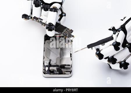 Main robotique la réparation de téléphone mobile sur fond blanc Banque D'Images