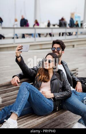 Espagne, Barcelone, happy young couple reposant sur un banc en tenant un selfies Banque D'Images