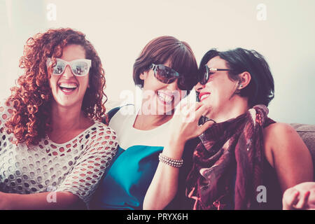 Trois jeunes femmes fou amis ayant beaucoup de plaisir à la maison sur le canapé. toutes avec des lunettes de soleil et sourires et laughi. fermer veuillez nous contacter f