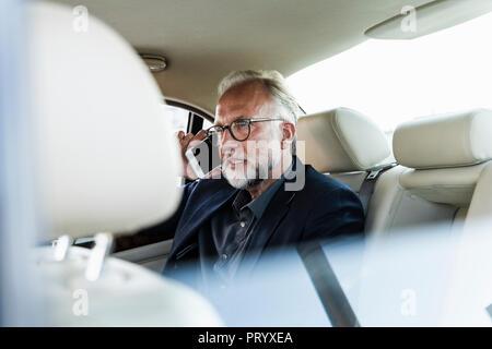 Mature businessman assis sur la banquette arrière en voiture, parler au téléphone Banque D'Images