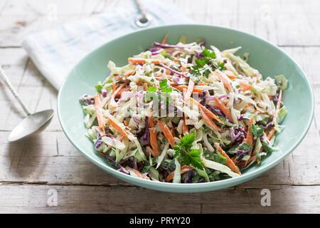 Coleslaw de choux, carottes et diverses herbes avec de la mayonnaise dans un grand plat sur un fond de bois. Banque D'Images