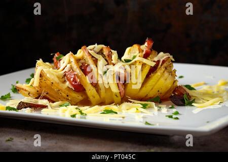 Pommes de terre accordéon remplie de bacon, saucisses et fromage aux herbes sur la plaque Banque D'Images