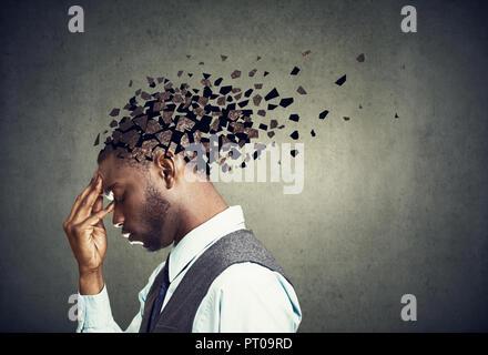 La perte de mémoire en raison de la démence ou des lésions cérébrales. Profil de côté d'un homme triste de perdre des parties de tête comme symbole d'une diminution de l'esprit. Banque D'Images
