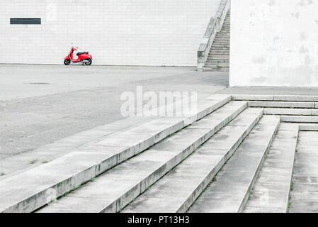 Scooter rouge solitaire contre mur blanc en arrière-plan et abondamment avec de l'environnement urbain en premier plan Banque D'Images