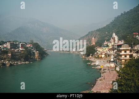 Vue de la rivière Ganga et Lakshman Jhula bridge dans Rishikesh. montagnes dans la brume. smog sur la ville. Banque D'Images