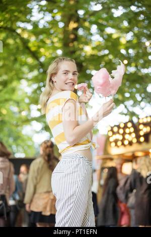 Portrait de jeune femme avec de la barbe à papa rose festival sur streetfood Banque D'Images