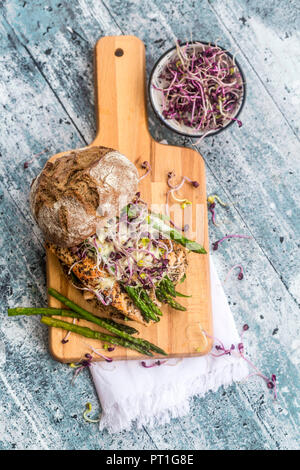 Burger de saumon aux asperges vertes et rouges cress sur planche à découper Banque D'Images