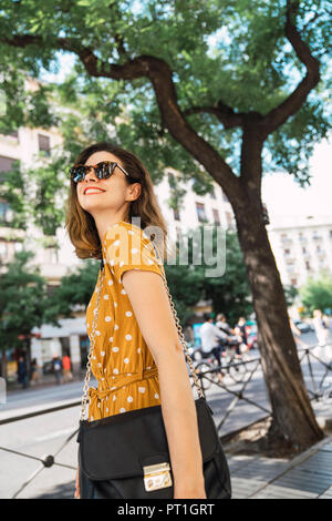 Belle femme portant robe jaune à pois, marcher dans la ville Banque D'Images