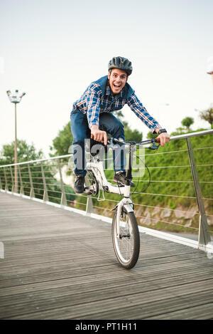 Jeune homme faisant des tours avec un vélo pliant Banque D'Images