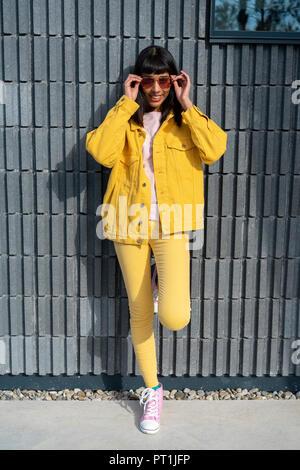 Jeune femme portant des vêtements jeans jaune Banque D'Images