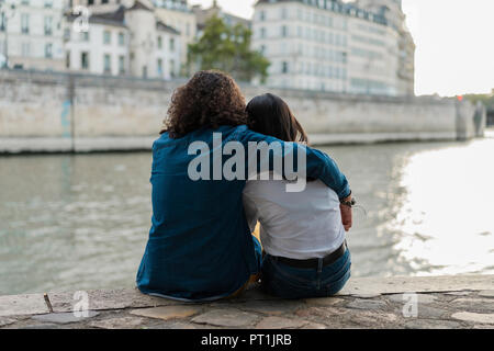France, Paris, vue arrière du jeune couple assis sur un mur à fleuve Seine Banque D'Images