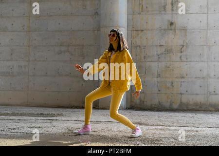 Femme portant des vêtements jeans jaune, la danse Banque D'Images