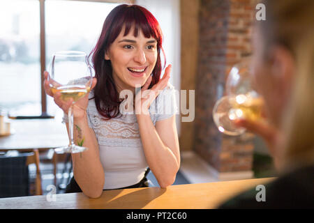 Happy female friends at home drinking white wine Banque D'Images