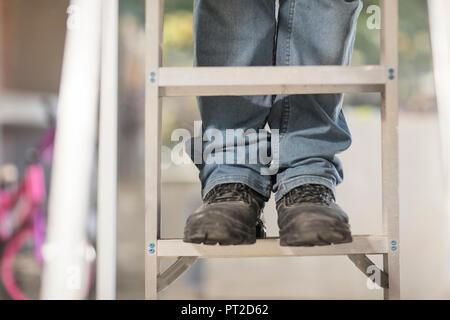 Homme debout sur l'échelle, vue partielle Banque D'Images