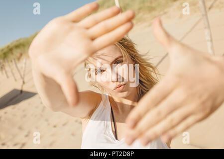Portrait de jeune femme blonde à la plage, l'élaboration de cadre avec ses mains Banque D'Images