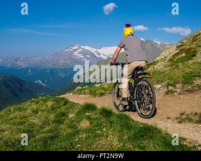 Italie Lombardie, Passo di Val Viola, Man riding e-bike dans les montagnes avec action cam sur son casque Banque D'Images
