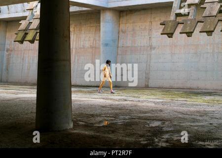 Jeune femme portant des vêtements jeans jaune, randonnée pédestre Banque D'Images