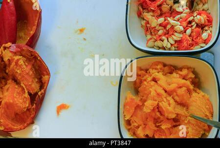 La préparation à la citrouille traditionnelle avec remplissage, pâte et ingrédients sur fond rustique foncé, vue du dessus, de style rétro, cadre. Banque D'Images