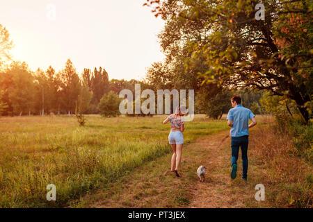 Jeune couple walking dog pug en forêt d'automne. Chiot heureux le long et avoir du plaisir à jouer avec le maître à l'extérieur. Banque D'Images