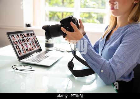 Femme Rédactrice Holding Photo reflex numérique avec un ordinateur portable sur 24
