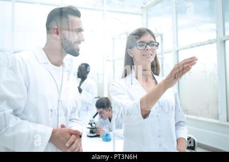 Les jeunes scientifiques en blouse blanche dans le laboratoire de sciences sont en train de discuter de l'formule dérivée Banque D'Images