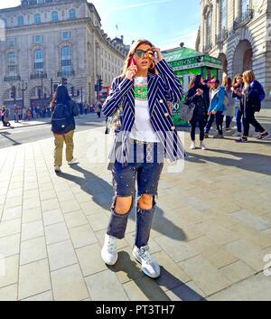 Jeune femme à la mode sur son téléphone portable à Piccadilly Circus, Londres, Angleterre, Royaume-Uni. Banque D'Images