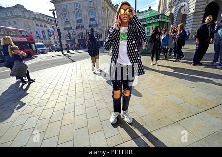 Jeune femme à la mode avec ripped jeans du genou sur son téléphone portable à Piccadilly Circus, Londres, Angleterre, Royaume-Uni. Banque D'Images