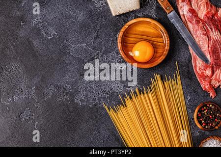 Ingrédients pour les pâtes à la Carbonara sur fond sombre, vue du dessus. Banque D'Images