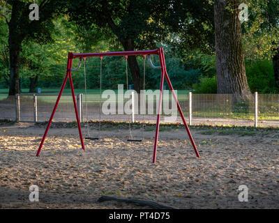 Image de la balançoire rouge isolé dans une aire de sable Banque D'Images