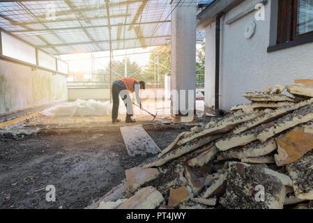 Accueil réparation. La reconstruction de l'imperméabilisation et l'isolation d'un toit terrasse -, dépose et stockage de l'ancien isolant (polyuréthane). Travailleur rétroéclairé Banque D'Images