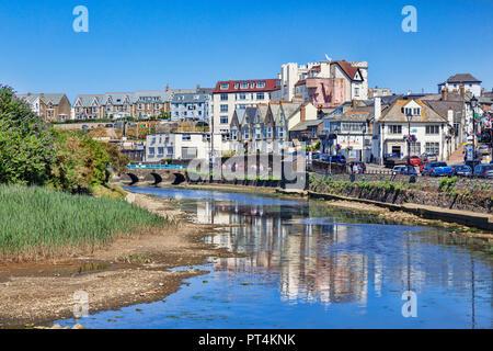 6 Juillet 2018: Bude, Cornwall, UK - maisons et entreprises dans la ville balnéaire, reflétée dans la rivière Neet, sur une chaude journée d'été.