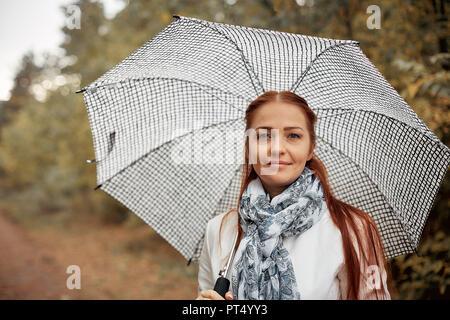 Beau portrait femme d'âge moyen aux cheveux rouges avec un parapluie dans le parc à l'apparence d'un jour d'automne Banque D'Images