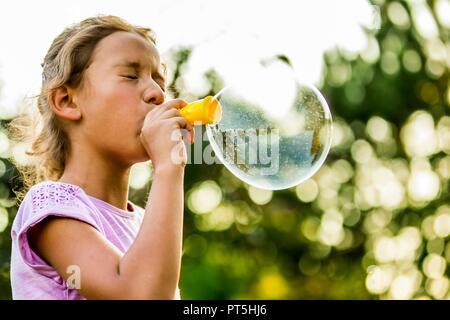 Girl blowing bubbles avec bubble wand dans parc. Banque D'Images