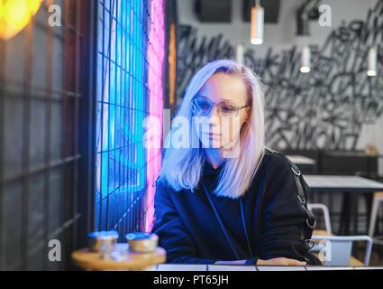 Hipster triste fille blonde à lunettes assis au bar près de l'enseigne au néon Banque D'Images