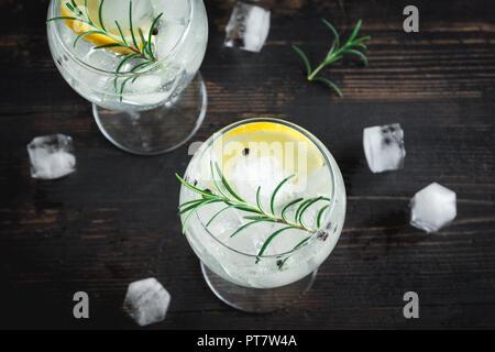 Boire de l'alcool (gin tonic cocktail) avec du citron, du romarin et de la glace sur la table rustique en bois noir, copie espace, vue du dessus. Verre à cocktail glacé au citron et Banque D'Images