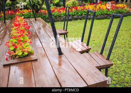 Chaises en bois naturel et une table dans le parc en milieu de gamme d'ornement décoratif des jardins de fleurs. Activités familiales en plein air d'été, loisirs, Refre Banque D'Images