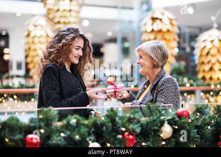 Une adolescente à présent donner grand-mère dans un centre commercial à Noël. Banque D'Images