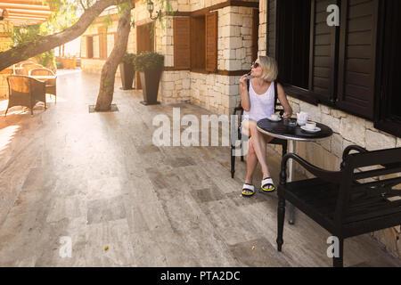 Une jeune femme est assise à une table dans un café sur la rue et apprécie son café du matin. Banque D'Images