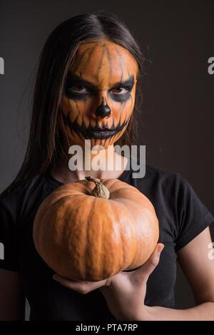 Portrait d'une jeune fille dans un terrible make-up en l'honneur d'Halloween sur un fond noir avec une citrouille Banque D'Images