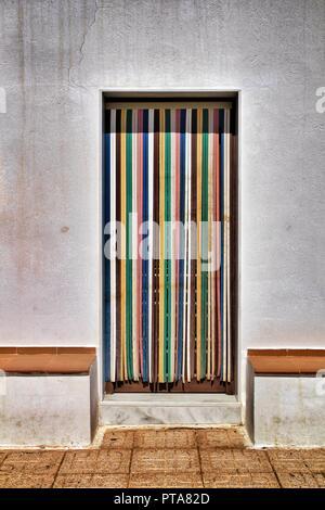 Rideau à rayures colorées et sur la porte de maison de village à Almeria, Espagne Banque D'Images