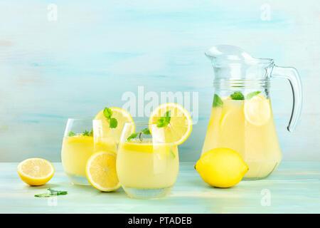 Une vue de côté de la limonade faite maison dans les verres et un pichet, avec des citrons frais et menthe, sur un fond bleu sarcelle with copy space