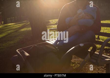 L'alimentation de son père lait Bébé garçon dans le parc Banque D'Images